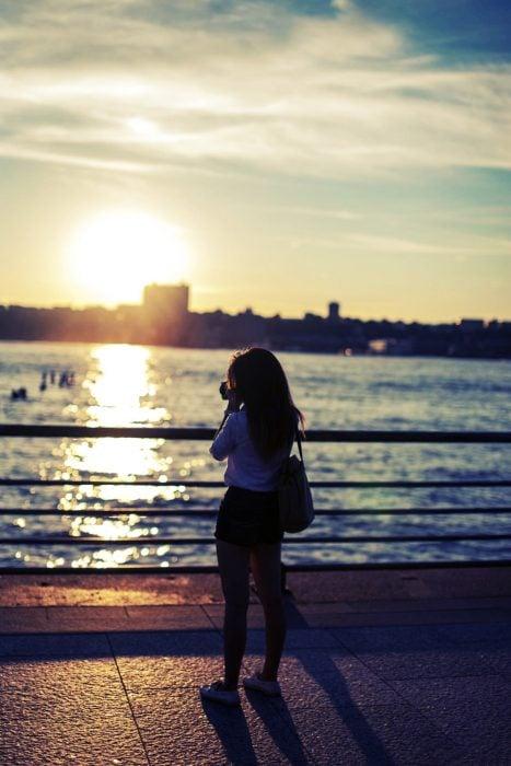 chica tomando fotografías a un atardecer