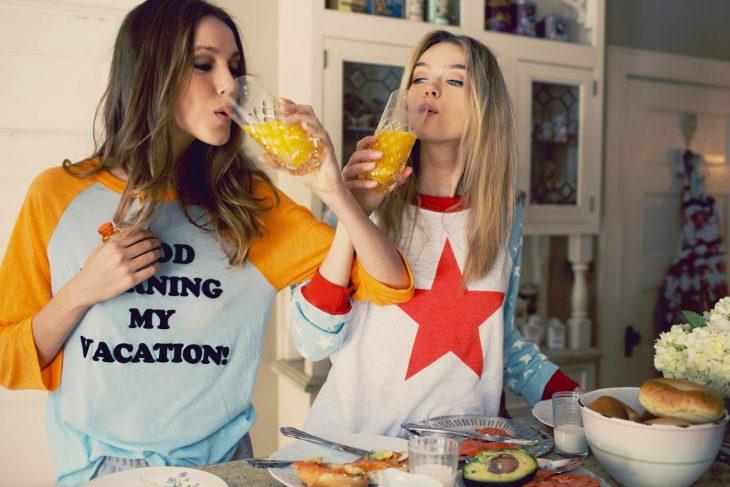 Chicas tomando vitaminas con jugo de naranja