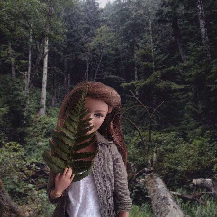 Fotografías de Barbie hipster en el bosque con una hoja en la mano