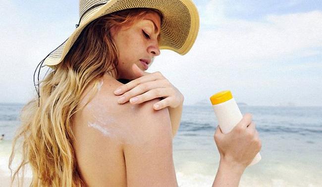 Chica poniéndose protector solar en la piel