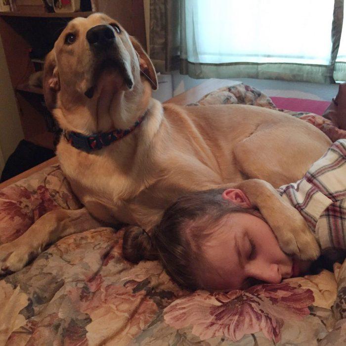 Perro con la pata arriba de su dueña dormida