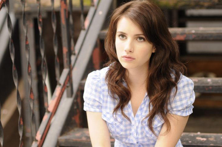 Emma roberts sentada en unas escaleras con cara enojada