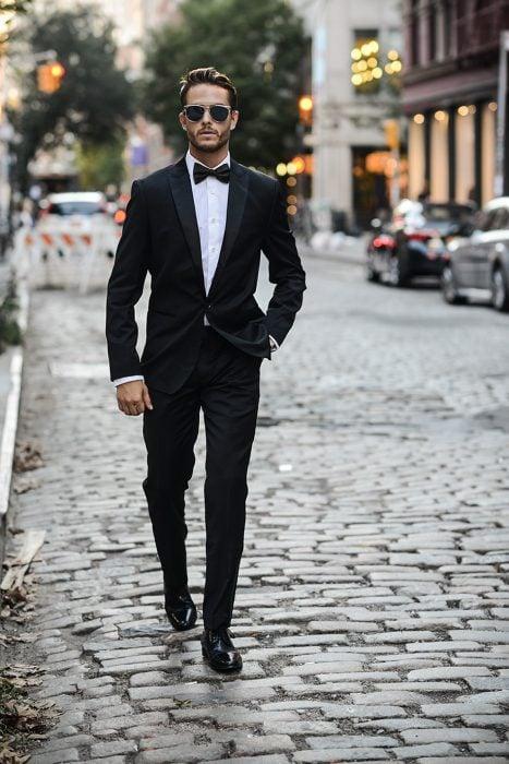 Hombre usando un traje y caminando por la calle