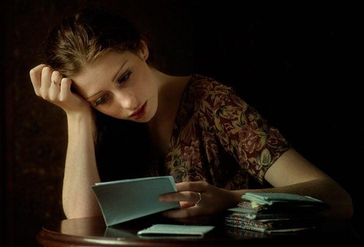 Chica leyendo una carta pensativa