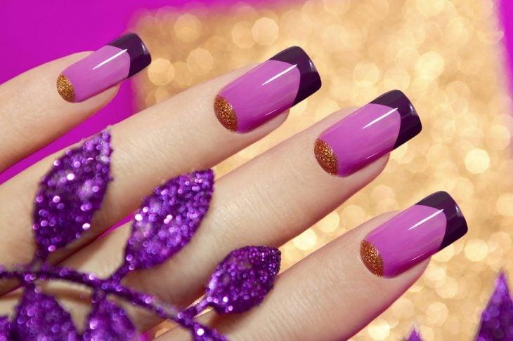 Uñas decoradas con esmaltes en rosa, morado y dorado