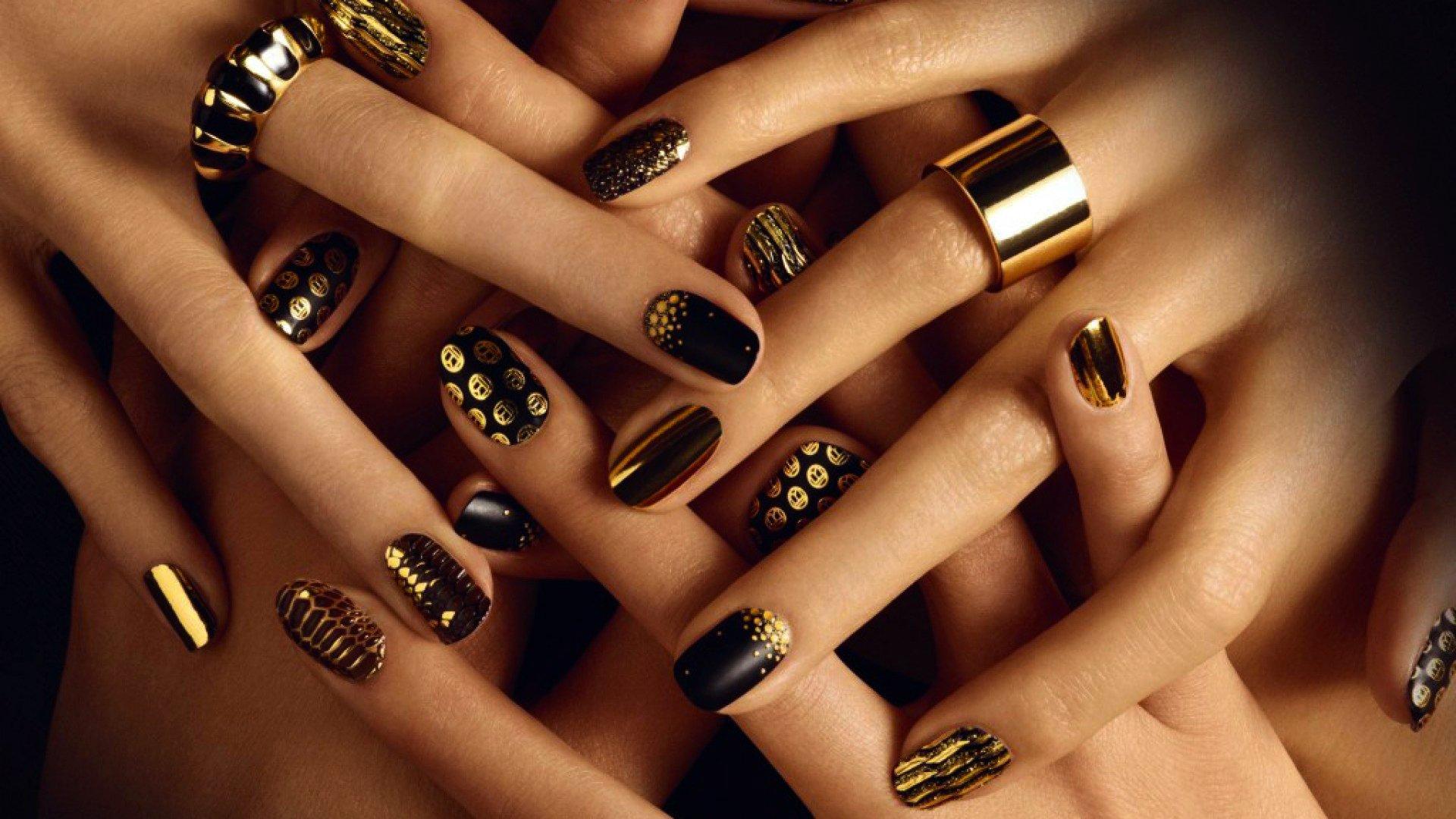 Uñas pintadas con esmalte en color negro y dorado