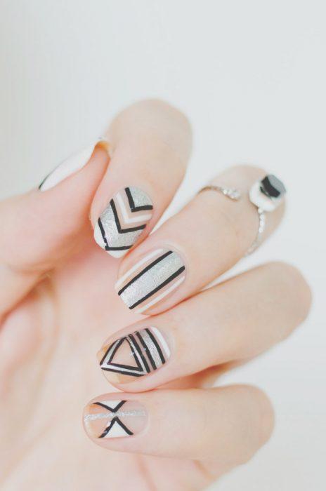 Uñas de color blanco con diseños de lineas en negro