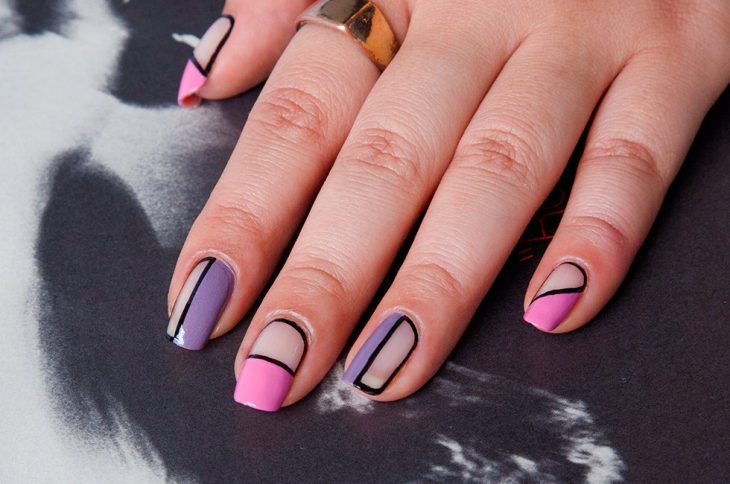 Uñas pintadas con esmalte rosa y morado