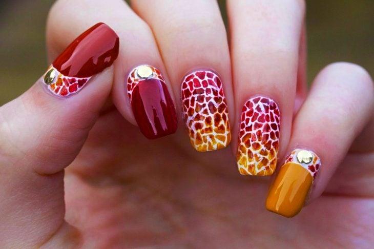 Uñas pintadas con diseños en rojo y naranja