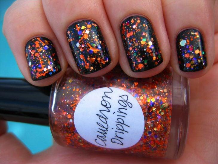 Uñas negras con gliter color naranja