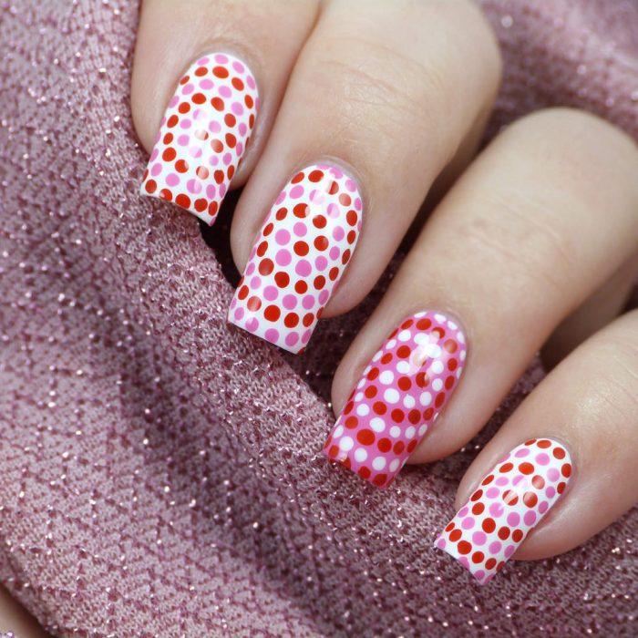 Uñas con puntos rosas, rojas y blancos en espiral