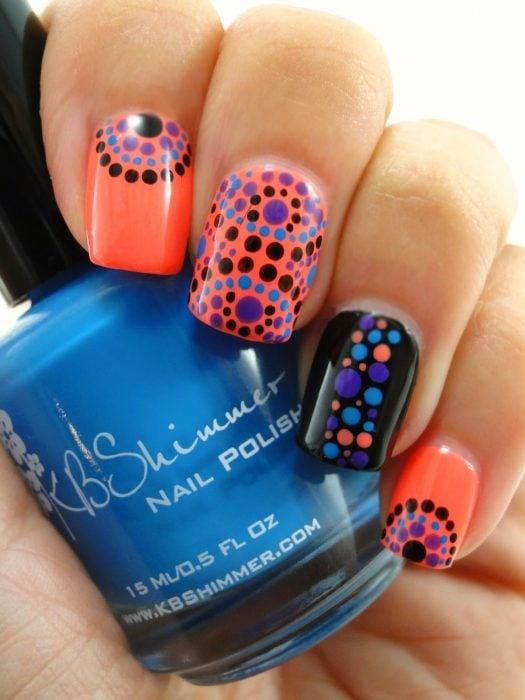 Uñas naranja y negras con puntos de colores