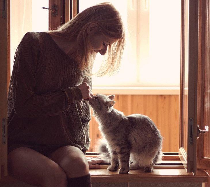 Chica sentada acariciando a un gato