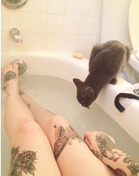 Chica bañándose mientras el gato toma agua