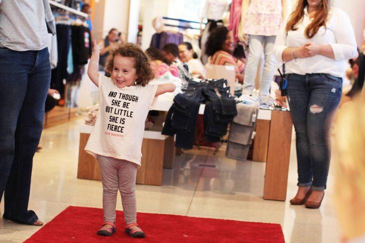 Niña que no tiene un brazo parada sobre una alfombra roja en una tienda