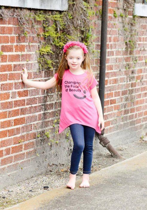 Niña usando una camisa rosa mientras está recargada en una pared
