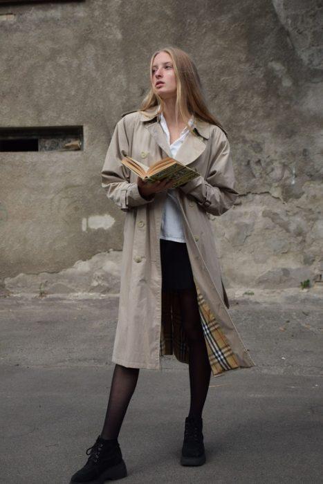 Chica con un libro en la mano parada en medio de la calle meintras observa todo a su alrededor