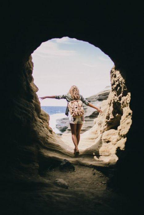 Chica atravesando una cueva que da hacia el mar