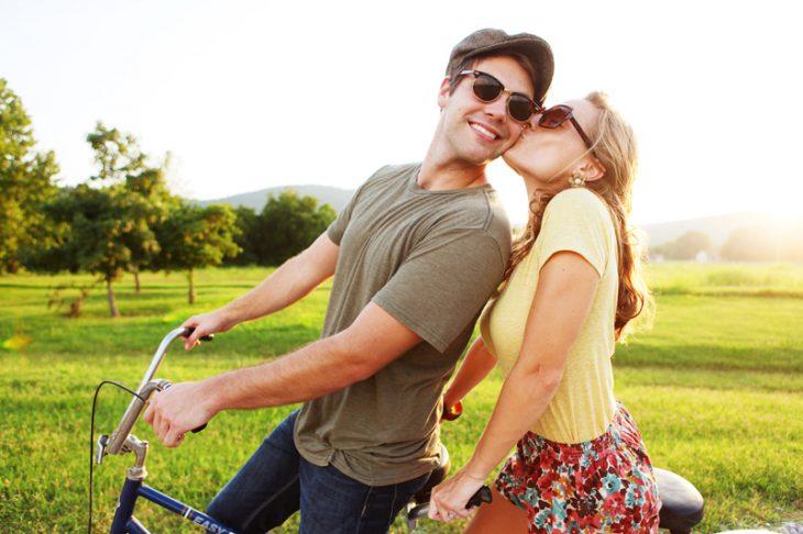 Chica besando la mejilla de un chico mientras pasean en bicicleta