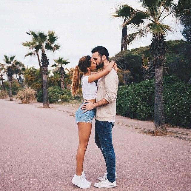 Pareja de novios abrazados besándose en medio de la calle