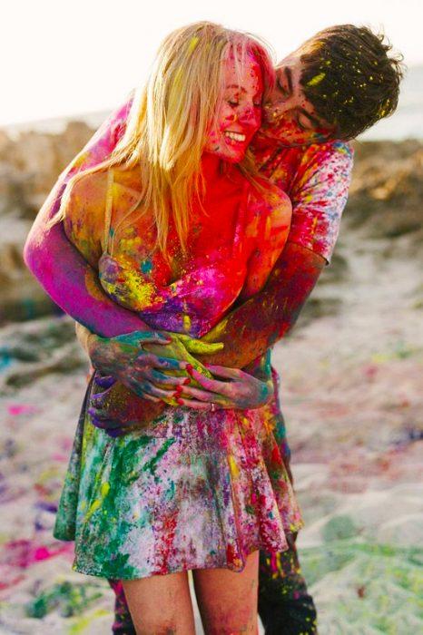 Pareja de novios llenos de pintura abrazados