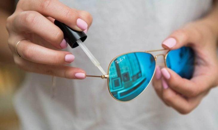 Chica colocándole esmalte de uñas transparente a unos lentes