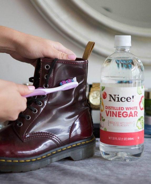 Chica limpiando unas botas Dr. marteen con vinagre y un cepillo de dientes