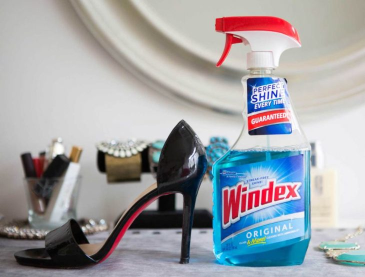 Zapatos de charol colocados junto a un limpiador de vidrios