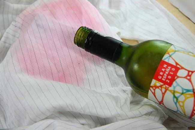 Chica virtiendo vino sobre una camisa con manchas