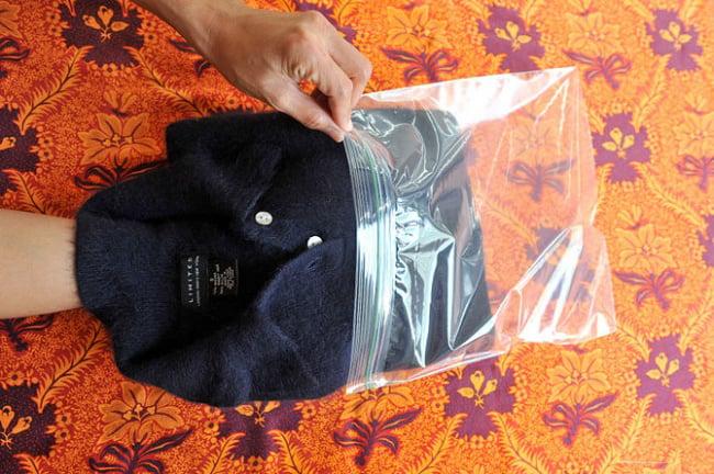 Chica metiendo un suéter dentro de una bolsa siplock