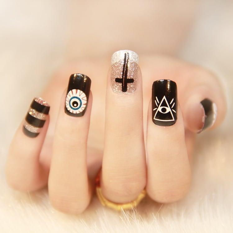 Uñas negras y plateadas con figuras blancas