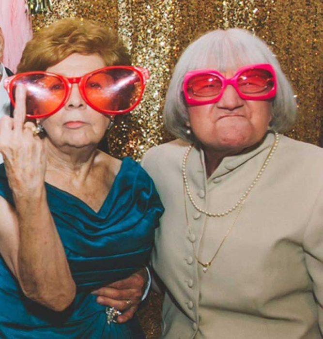 abuelitas en una cabina de fotos con lentes enormes y mostrando su dedo corazón