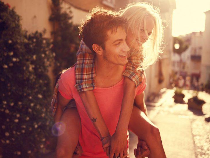 Chico cargando a una chica en la espalda mientras caminan