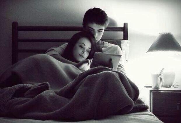 Pareja de novios recostados en la cama viendo una tablet
