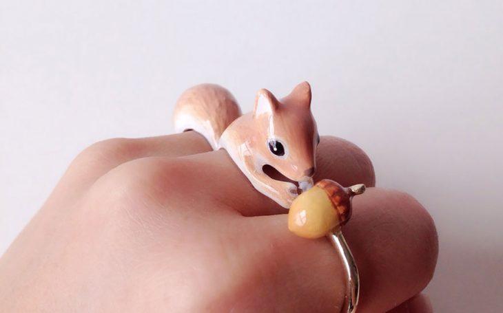 Mano de una chica mostrando su anillo en forma de ardilla