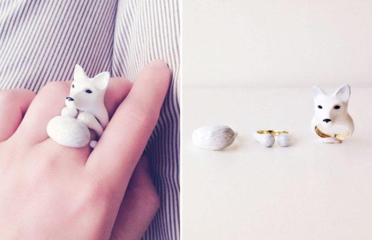 Mano de una chica mostrando su anillo en forma de zorro blanco