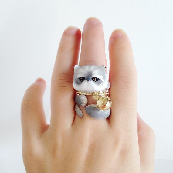 Chica mostrando su anillo en forma de gato