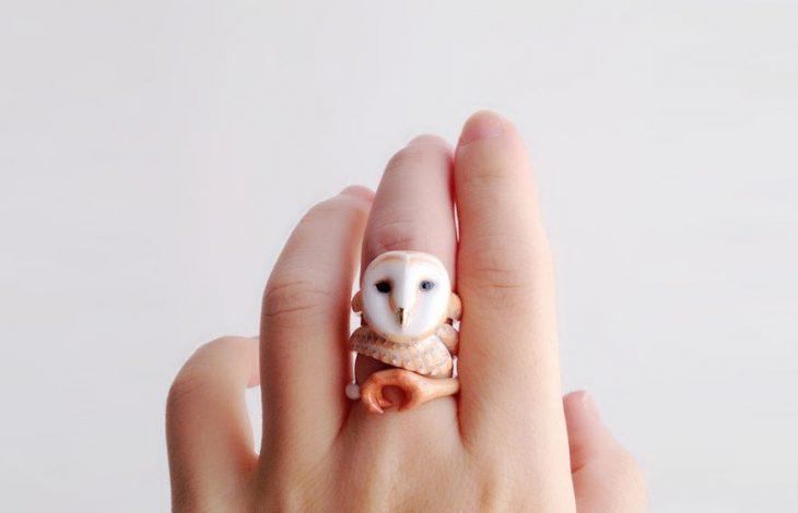 Mano de una chica mostrando su anillo en forma de búho