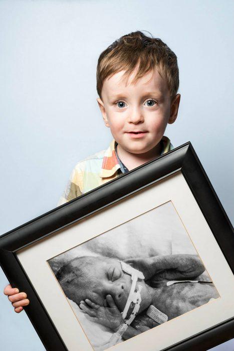 Niño sosteniendo un cuadro con una foto de el cuando era un bebé prematuro