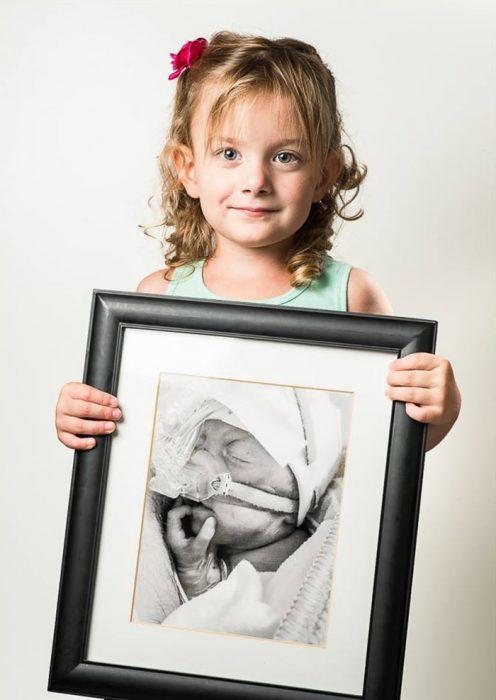 niña sosteniendo su fotografía de cuando nacio como una bebé prematura