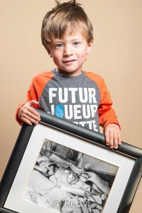 Niño sosteniendo una fotografía de él mismo cuando era bebé