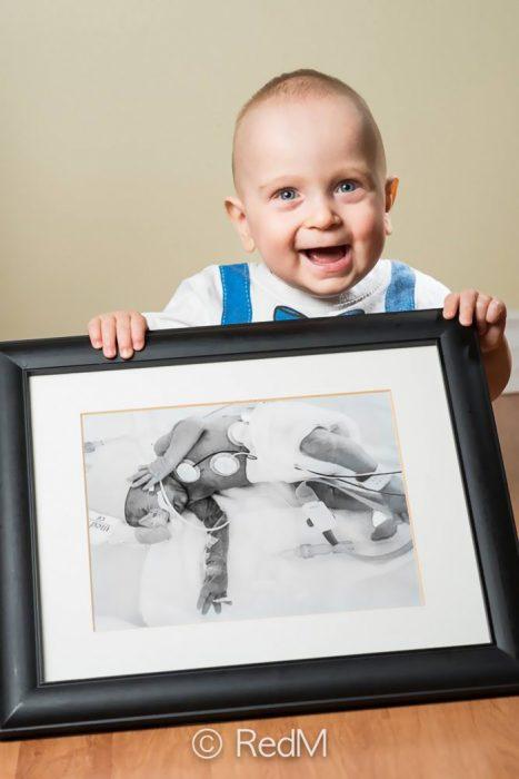 Niño sosteniendo una fotografía de él mismo cuando era un bebé prematuro