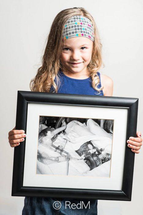 Niña sosteniendo una foto de ella misma ciuando estaba recien nacida
