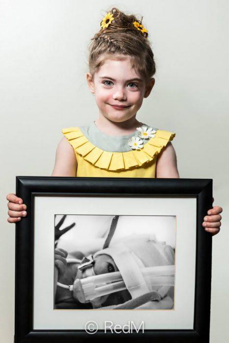 Niña vestida de amarillo sosteniendo una imagen de ella cuando era bebé y estaba en la incubadora