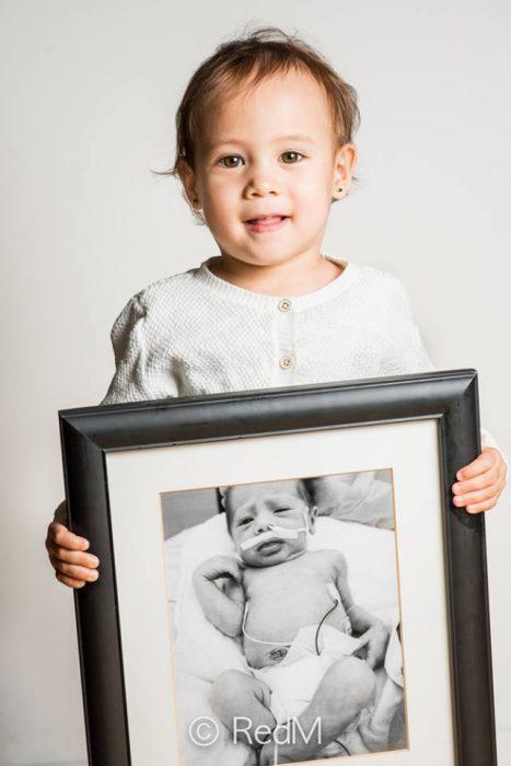 bebé sosteniendo una imagen de ella cuando era una bebé prematura