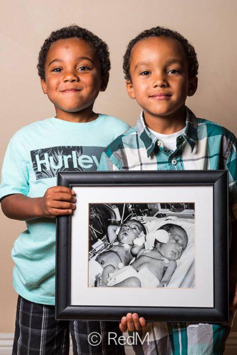 hermanos gemelos sosteniendo una fotografia de ellos cuando eran bebés