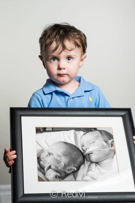 niño sosteniendo una fotografía de él y de su hermana cuando eran bebes prematuros