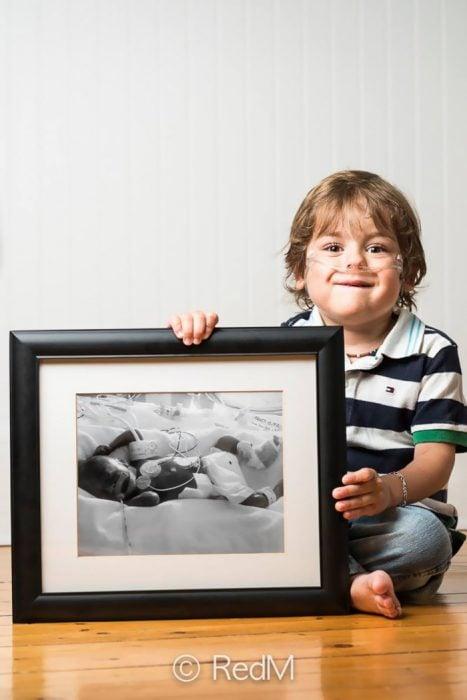 bebé sosteniendo una imagen de cuando estaba en la incubadora