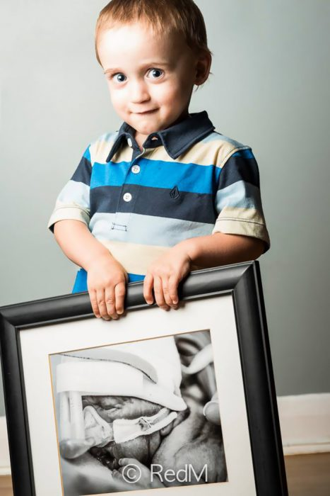 Niño sosteniendo una imagen de él cuando era un bebé que estaba en la incubadora