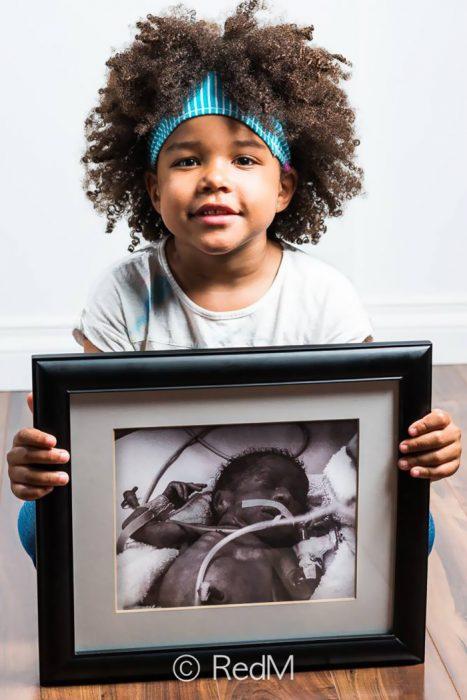 Niña sentada en el suelo sosteniendo una fotografía de ella cuando era bebé y estaba conectada a distintos tubos